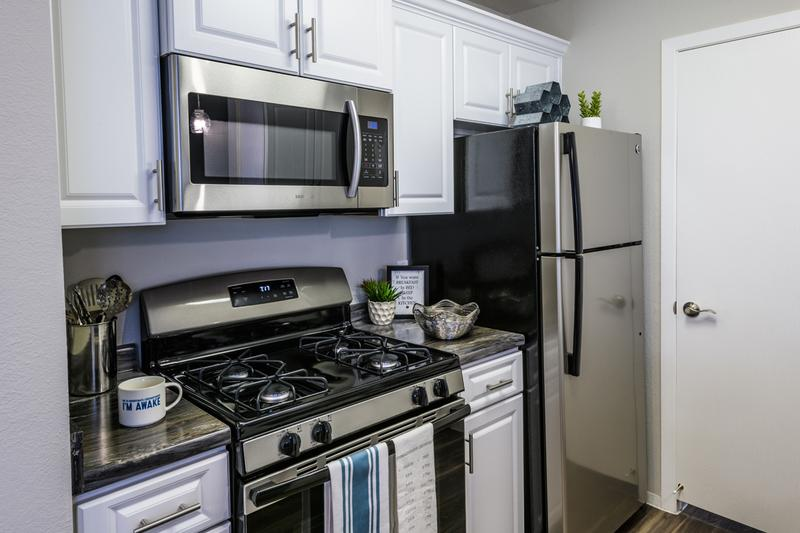 Renovated Kitchens - In Select Homes | Renovated kitchens featuring black fusion counter tops, wood-style flooring, and stainless steel appliances.