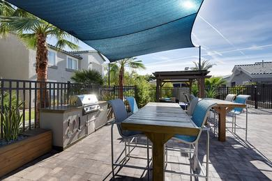 Outdoor Kitchen | Enjoy a cookout by the pool at our outdoor kitchen featuring a gas grill and tables.