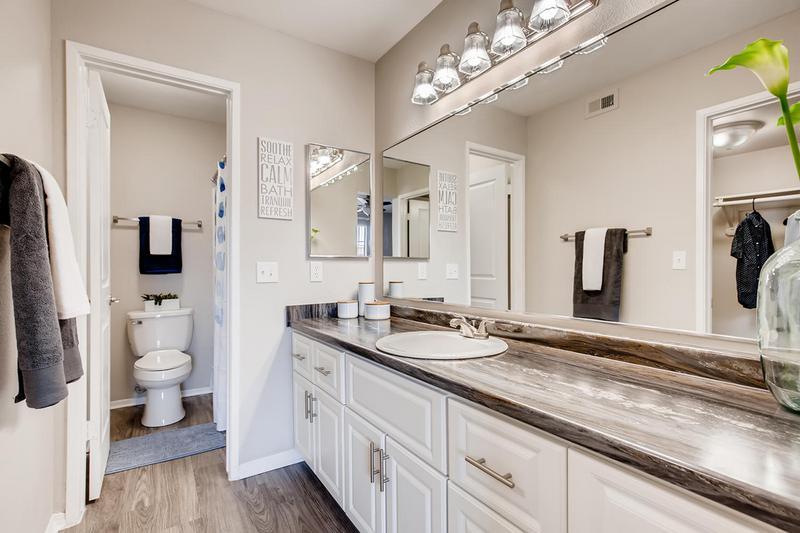 Master Bathroom | Spacious master bathrooms featuring black-fusion counter-tops, wood-style flooring, and large over-sized mirrors.
