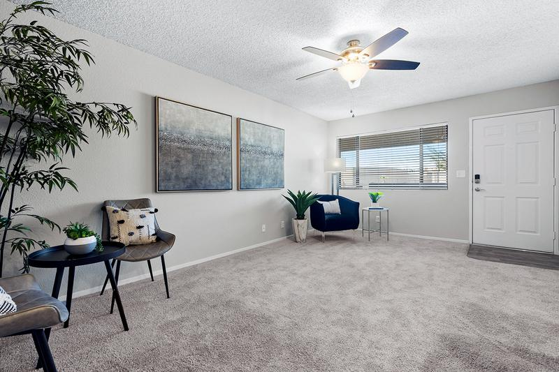 Living Room | Updated living rooms with plush carpeting and a ceiling fan.
