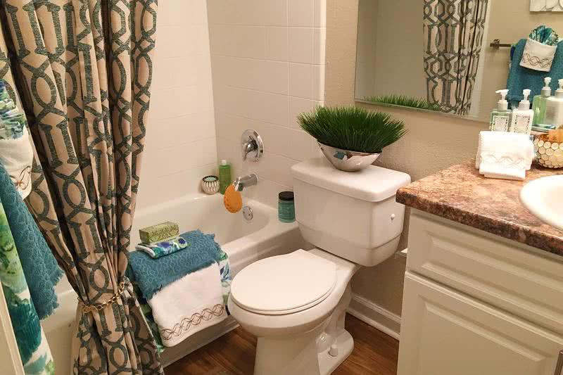 Bathroom | Updated bathrooms featuring hardwood flooring and large mirrors.
