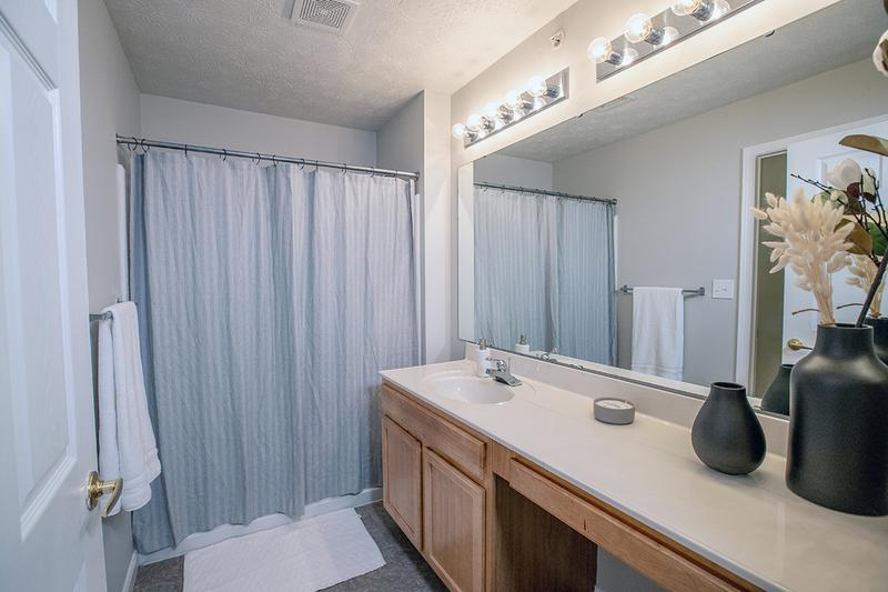 Master Bathroom | Master bathrooms featuring wood-style flooring and large mirrors.