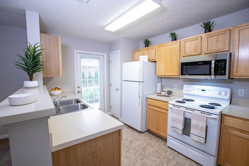 Kitchen | Fully applianced kitchens feature ample cabinetry, a microwave, and dishwasher.