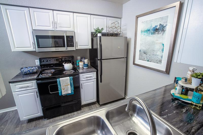 Renovated Kitchens | Newly renovated kitchens featuring stainless steel and black appliances and modern white cabinetry.