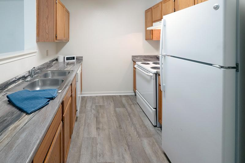 Galley Style Kitchen | Galley style kitchens featuring wood-style flooring, updated countertops, and ample cabinetry.