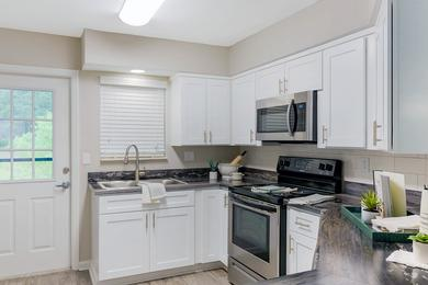 Brand New Designer Kitchens | Open concept kitchens featuring wood-style flooring and breakfast bar.