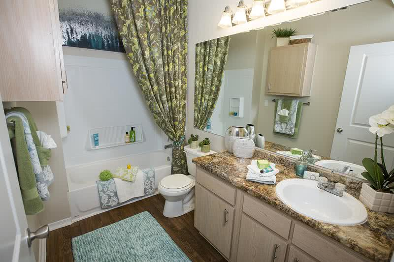 Bathroom | Newly remodeled bathrooms featuring granite-style counter tops, large mirrors, and garden tub.